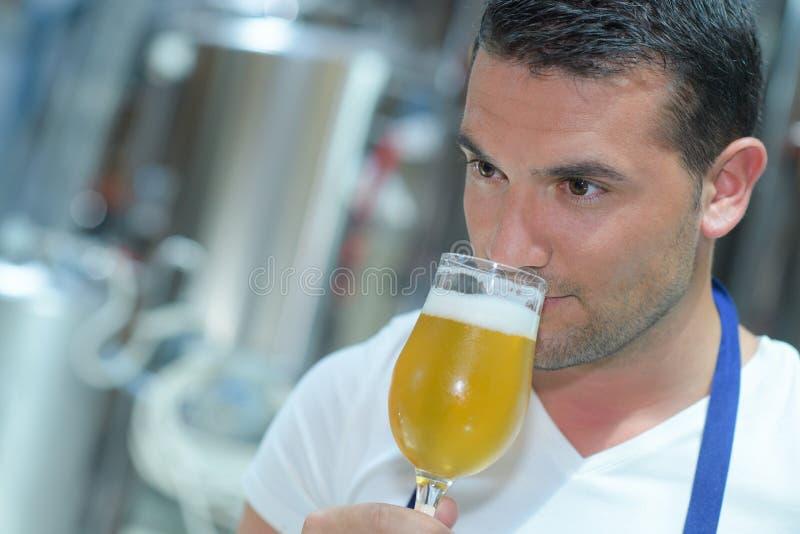 Zakończenie piwowar wącha piwo przy browar fabryką obrazy stock