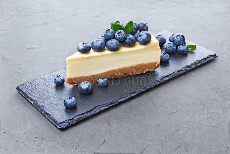 Zakończenie plasterek wyśmienicie domowej roboty cheesecake z świeżymi czarnymi jagodami na czerń łupku desce obraz royalty free