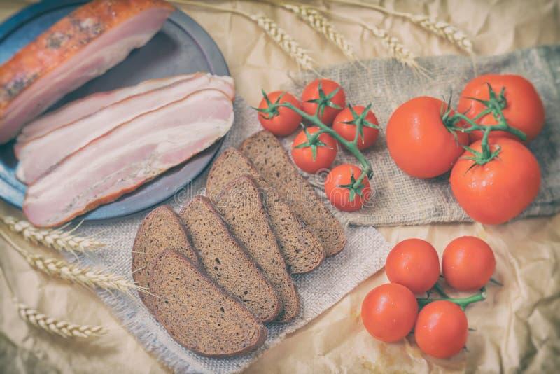 Zakończenie plasterki bekon, żyto czarny chleb, dojrzali czerwoni pomidory na pakować rzemiosło papier Odgórny widok świeże żywno zdjęcie royalty free