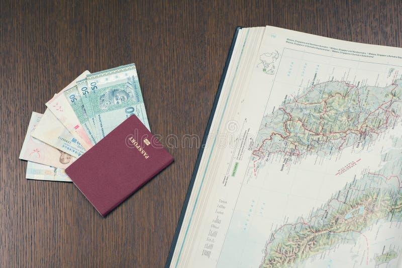 Zakończenie podróż biometryczny paszport z plikiem Malezyjskich ringgits amd otwierał mapę Malezja Planować wycieczki turysycznej obraz royalty free