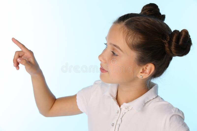 Zakończenie portret ładna dziecko dziewczyna patrzeje oddalonym i punktem z ona palcowa zdjęcia stock