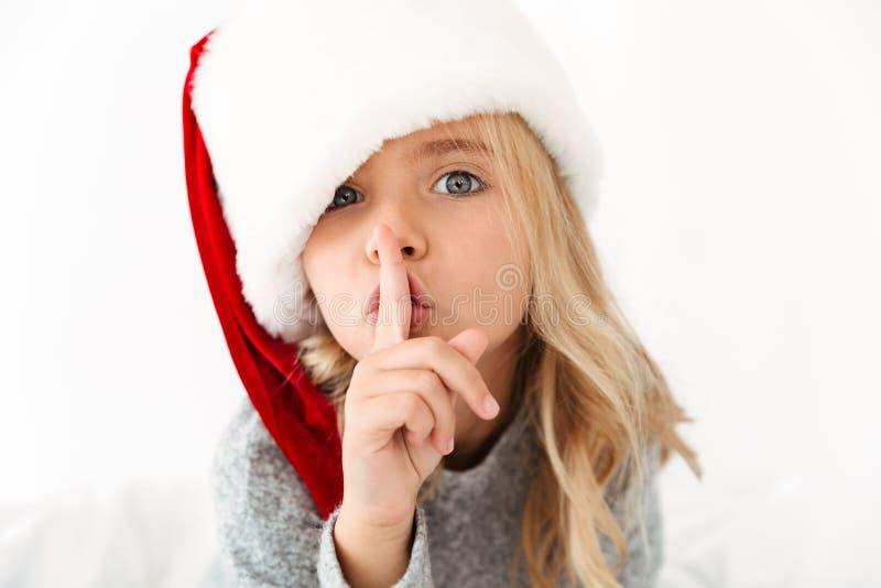 Zakończenie portret ładna mała dziewczynka w Santa ` s kapeluszowy pokazuje s zdjęcie stock