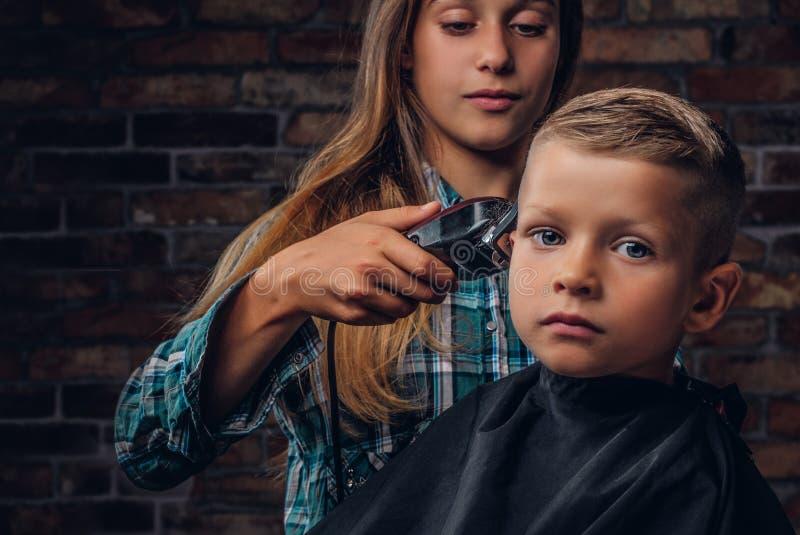 Zakończenie portret śliczna preschooler chłopiec dostaje ostrzyżenie Stara siostra ciie jej młodszego brata z drobiażdżarką obrazy royalty free