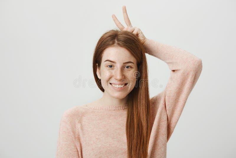 Zakończenie portret śliczny atrakcyjny europejski rudzielec kobiety modela mienia zwycięstwa znak za głową podczas gdy ono uśmiec zdjęcie stock