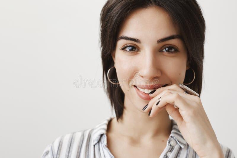 Zakończenie portret bajecznie powabna kobieta ono uśmiecha się sensually i trzyma rękę na wardze z krótkim ciemnym włosy, być wew zdjęcie stock