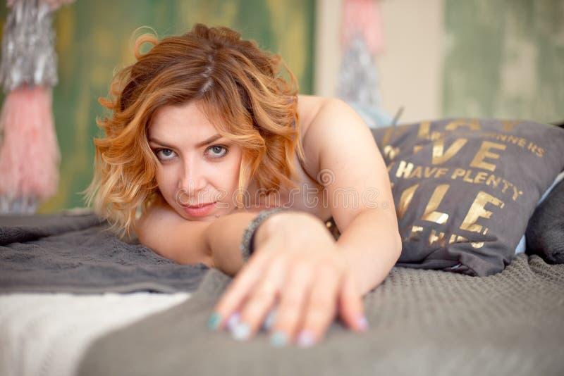 Zakończenie portret czerwona z włosami piękna kobieta kłama w kanapie w błękitnym seksownym staniku i cajgi Nęcąca młoda dziewczy obrazy stock