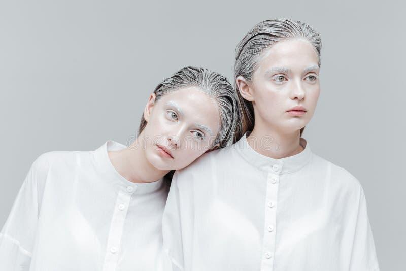 Zakończenie portret dwa kobiety w mądrze białych koszula zdjęcia stock