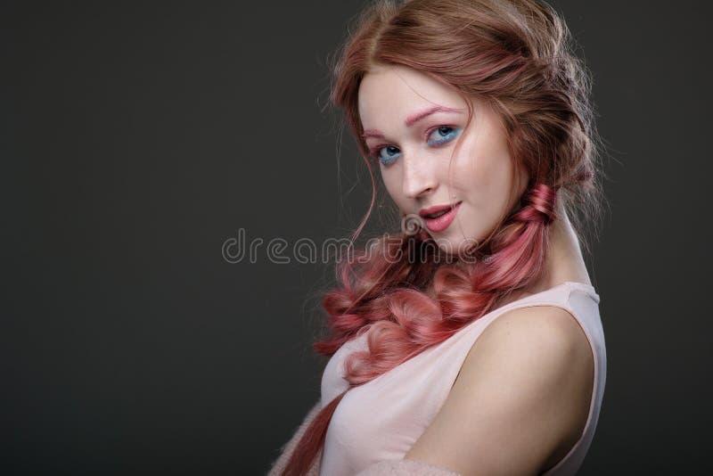 Zakończenie portret dziewczyna z różowym włosy w warkoczy, menchii i błękita makeup, stoi w okręgu na ciemnym tle figlarnie obraz royalty free