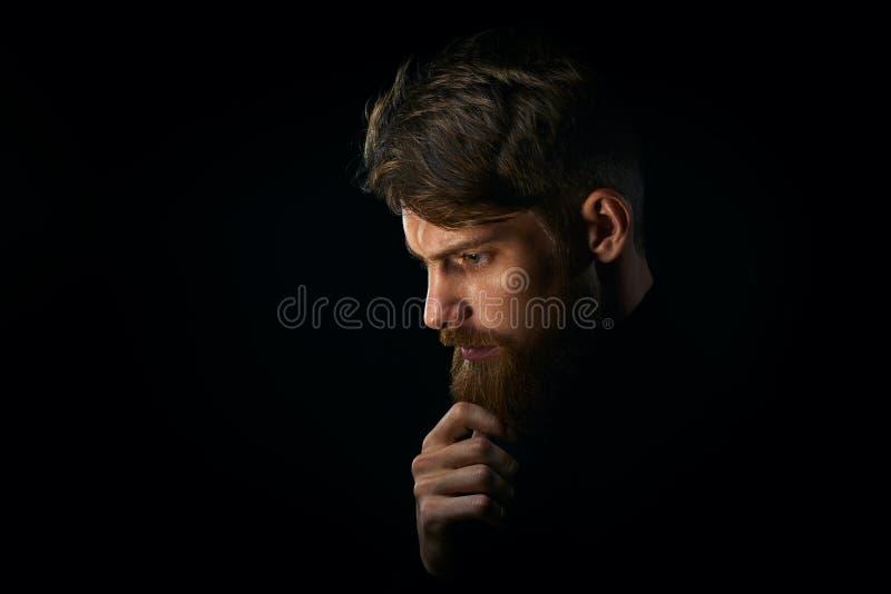 Zakończenie portret intrygująca młody człowiek wzruszająca broda patrzeje obrazy stock