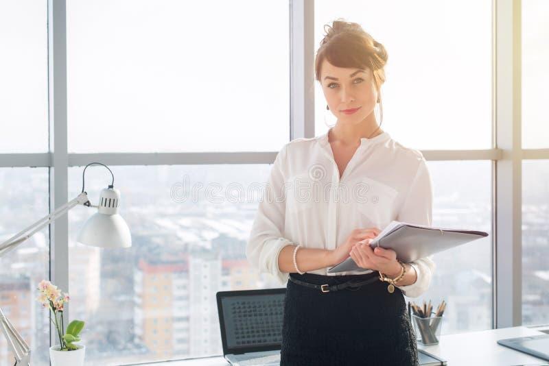 Zakończenie portret młody ufny żeński biurowy kierownik przy jej miejscem pracy, przygotowywający dla robić biznesowemu zadaniu obraz royalty free