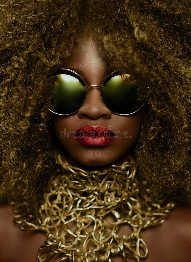 Zakończenie portret magiczny złoty amerykanin afrykańskiego pochodzenia kobiety model w masywnych okularach przeciwsłonecznych z  zdjęcia stock