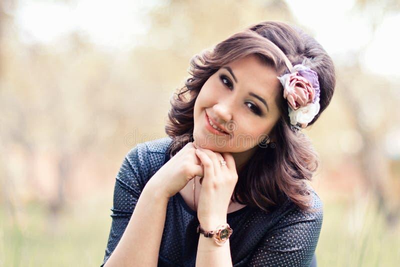 Zakończenie portret piękna, śliczna dziewczyna z wiankiem, różani czerwieni, beżu i białych kwiaty, siedzi outdoors w wiośnie, la zdjęcie royalty free