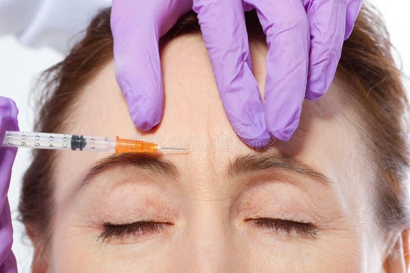 Zakończenie portret piękna wiek średni lekarka i kobieta wręcza robić botox zastrzykowi odizolowywającemu na białym tle kolagen obrazy stock