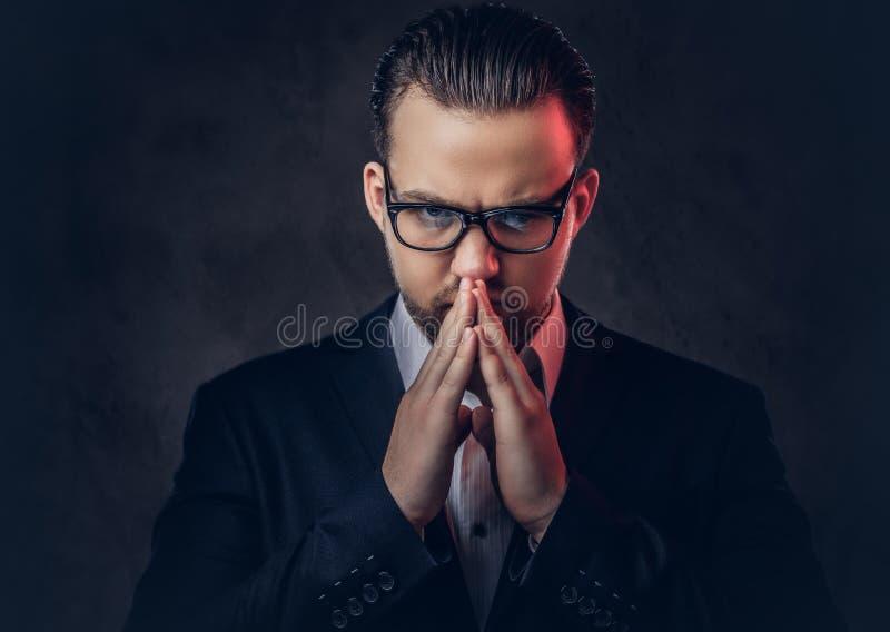 Zakończenie portret rozważny elegancki biznesmen z poważną twarzą w eleganckim formalnym kostiumu i szkłach na zmroku zdjęcia stock