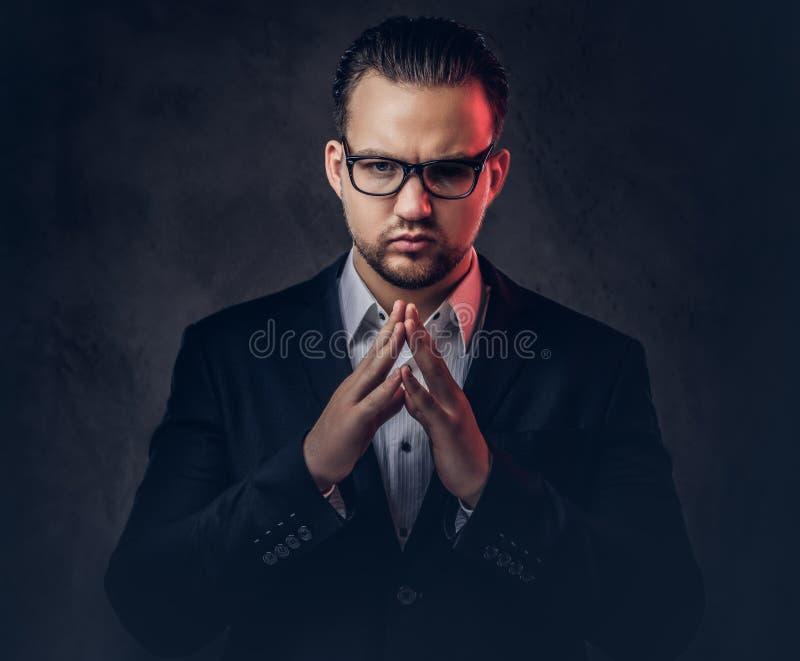 Zakończenie portret rozważny elegancki biznesmen z poważną twarzą w eleganckim formalnym kostiumu i szkłach na zmroku fotografia royalty free