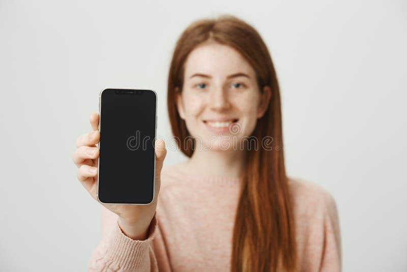 Zakończenie portret rudzielec europejskiej kobiety reklamowy smartphone, ono uśmiecha się szeroko, zamazujący podczas gdy ostrość fotografia royalty free