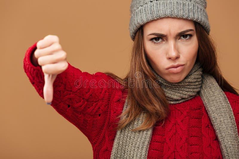 Zakończenie portret wzburzona kobieta w zimie odziewa pokazywać kciuk fotografia stock