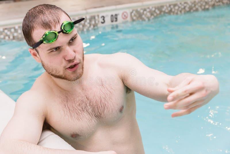 Zakończenie potomstwa manstanding w basenie i opowiadać obraz stock