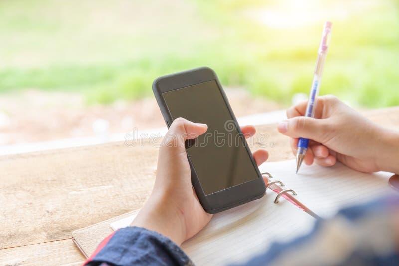 Zakończenie przypadkowa kobiety ręka up trzyma mobilnego smartphone i writei zdjęcie stock