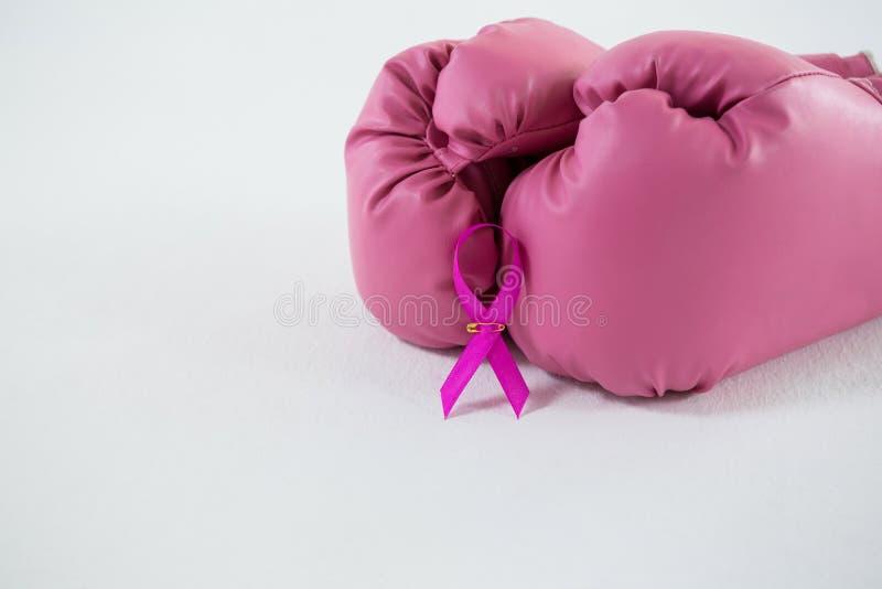 Zakończenie różowy nowotwór piersi świadomości faborek z bokserskimi rękawiczkami dobierać do pary zdjęcia stock