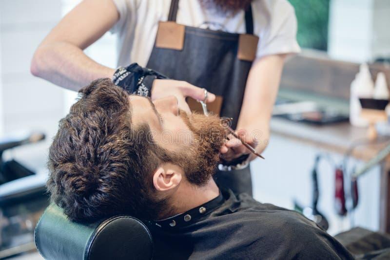 Zakończenie ręka fryzjer męski używa nożyce podczas gdy żyłujący fotografia royalty free