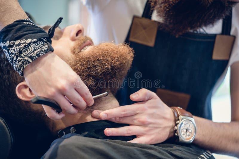 Zakończenie ręka fryzjer męski używa nożyce podczas gdy żyłujący obraz stock