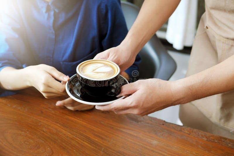 Zakończenie ręka kelnerka słuzyć filiżankę kawy klient obraz stock