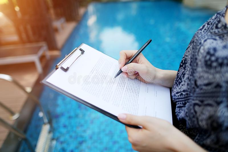 Zakończenie ręka młodej kobiety podpisywania dokument na tle słonecznego dnia basen Przód używać z Otwartym chrzcielnica licencja fotografia royalty free