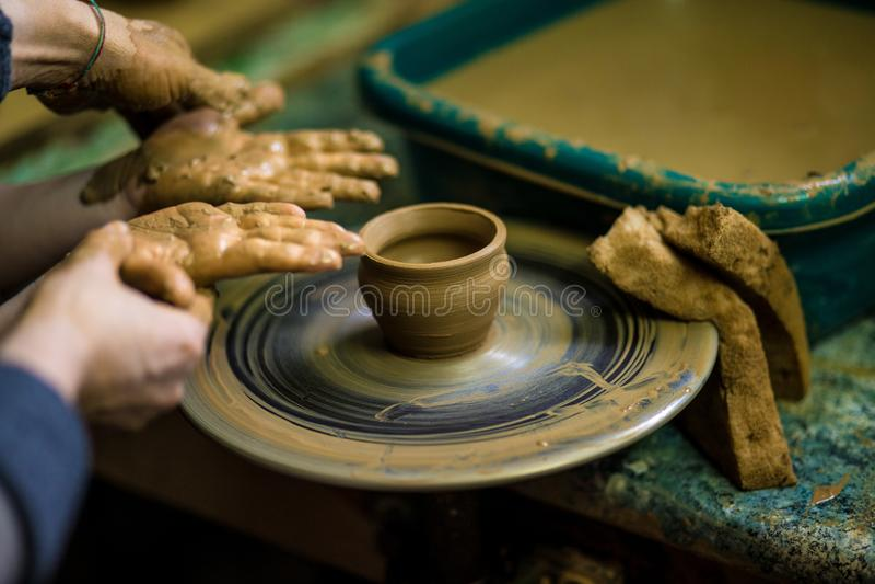 Zakończenie ręki garncarka w fartuchu robi wazie od gliny obrazy stock
