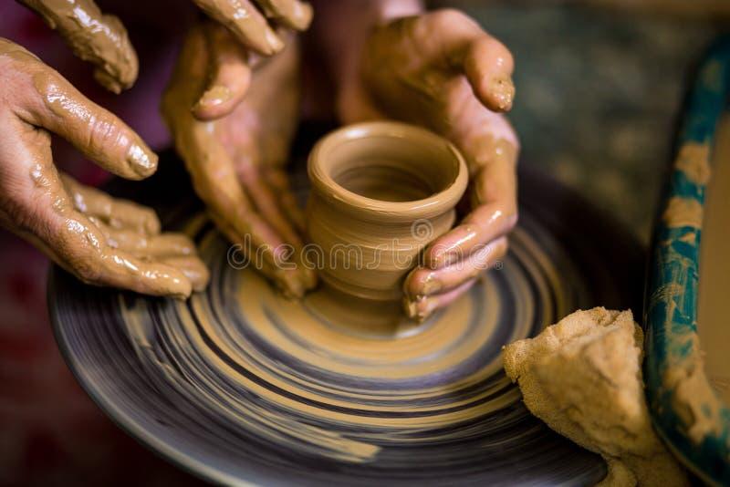 Zakończenie ręki garncarka w fartuchu robi wazie od gliny zdjęcia stock
