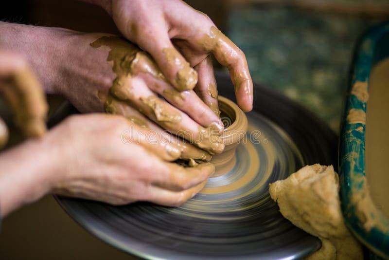 Zakończenie ręki garncarka w fartuchu robi wazie od gliny, selekcyjna ostrość obraz stock