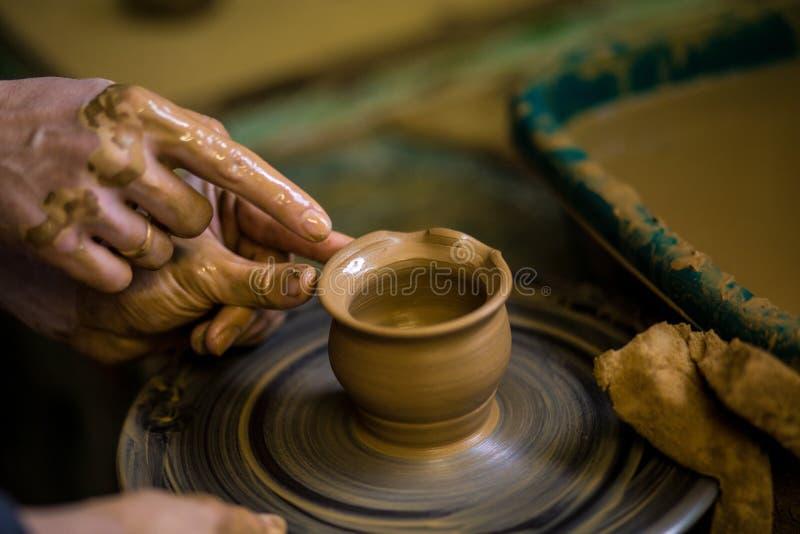 Zakończenie ręki garncarka w fartuchu robi wazie od gliny, selekcyjna ostrość Robić mię wpólnie obraz stock