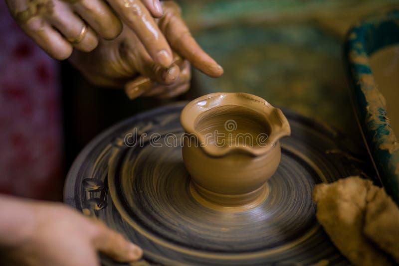 Zakończenie ręki garncarka w fartuchu robi wazie od gliny, selekcyjna ostrość Robić mię wpólnie fotografia royalty free