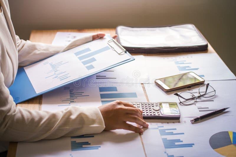 Zakończenie ręki kobiety biznes kalkulator i wykresów papiery na biurku z zmierzchem zdjęcia royalty free