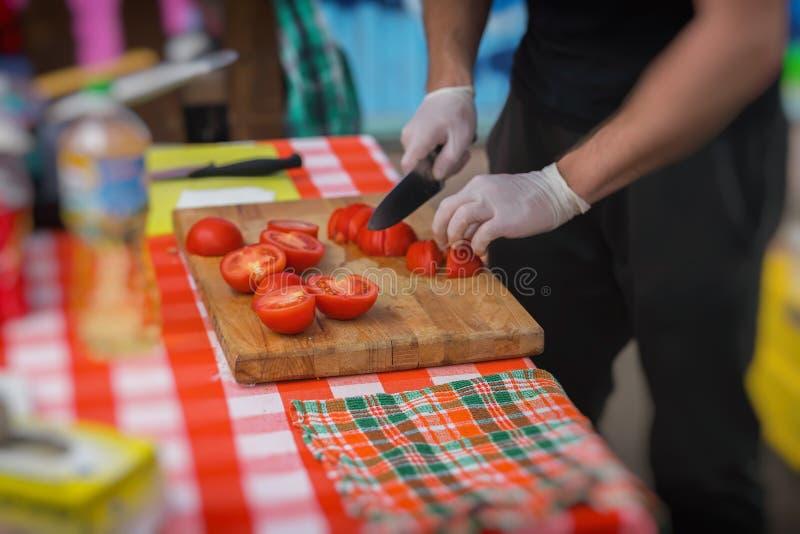 Zakończenie ręki Kucbarski mężczyzna w czarnym fartucha narządzania Fajita w parku, przecinanie świezi pomidory na drewnianej des obrazy stock