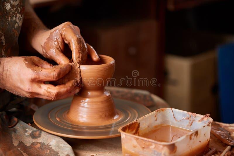 Zakończenie ręki męska garncarka w fartuch foremkach rzucają kulą od gliny, selekcyjna ostrość obraz royalty free