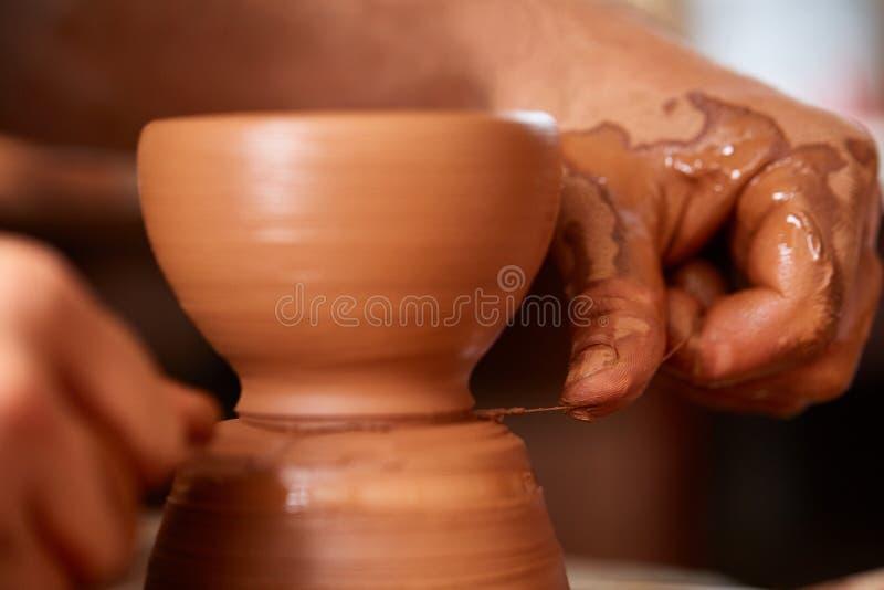 Zakończenie ręki męska garncarka w fartuch foremkach rzucają kulą od gliny, selekcyjna ostrość obrazy royalty free