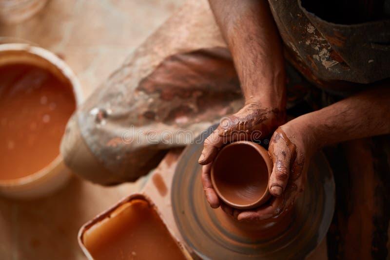 Zakończenie ręki męska garncarka w fartuch foremkach rzucają kulą od gliny, selekcyjna ostrość fotografia stock