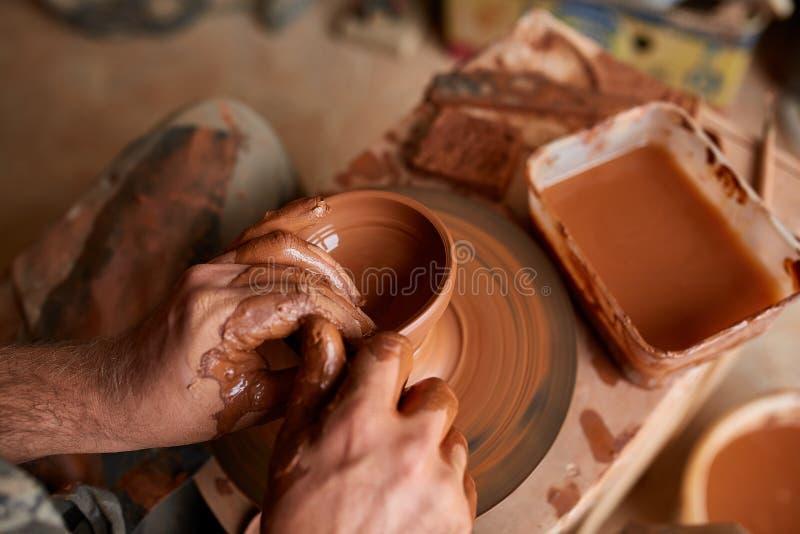 Zakończenie ręki męska garncarka w fartuch foremkach rzucają kulą od gliny, selekcyjna ostrość zdjęcie royalty free