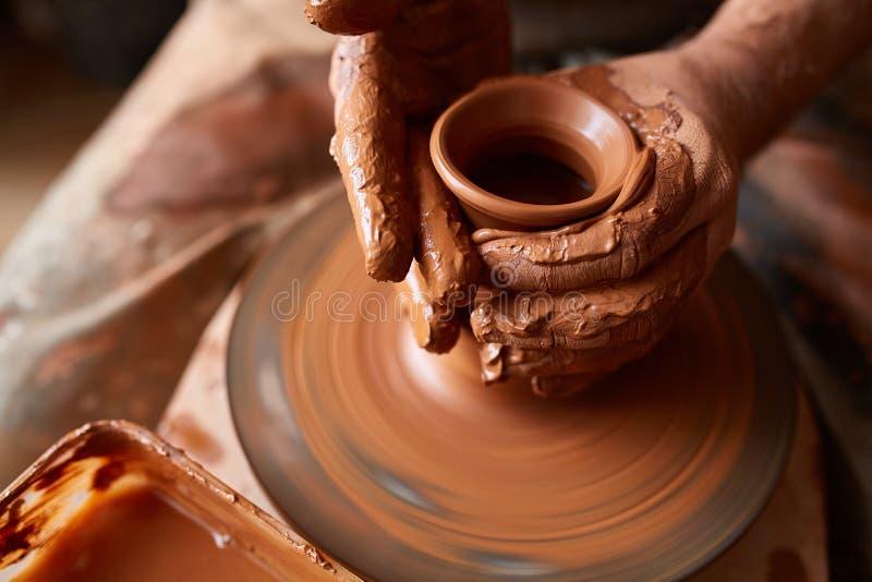 Zakończenie ręki męska garncarka w fartuch foremkach rzucają kulą od gliny, selekcyjna ostrość obrazy stock