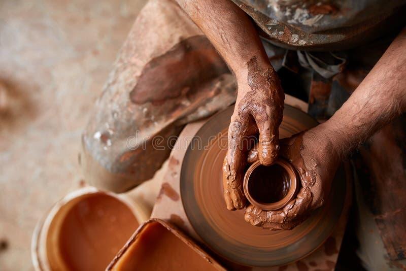 Zakończenie ręki męska garncarka w fartuch foremkach rzucają kulą od gliny, selekcyjna ostrość zdjęcia royalty free