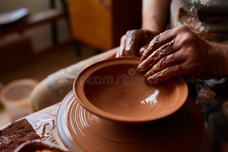 Zakończenie ręki męska garncarka w fartuch foremkach rzucają kulą od gliny, selekcyjna ostrość zdjęcia stock