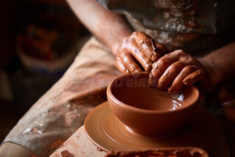 Zakończenie ręki męska garncarka w fartuch foremkach rzucają kulą od gliny, selekcyjna ostrość obraz stock