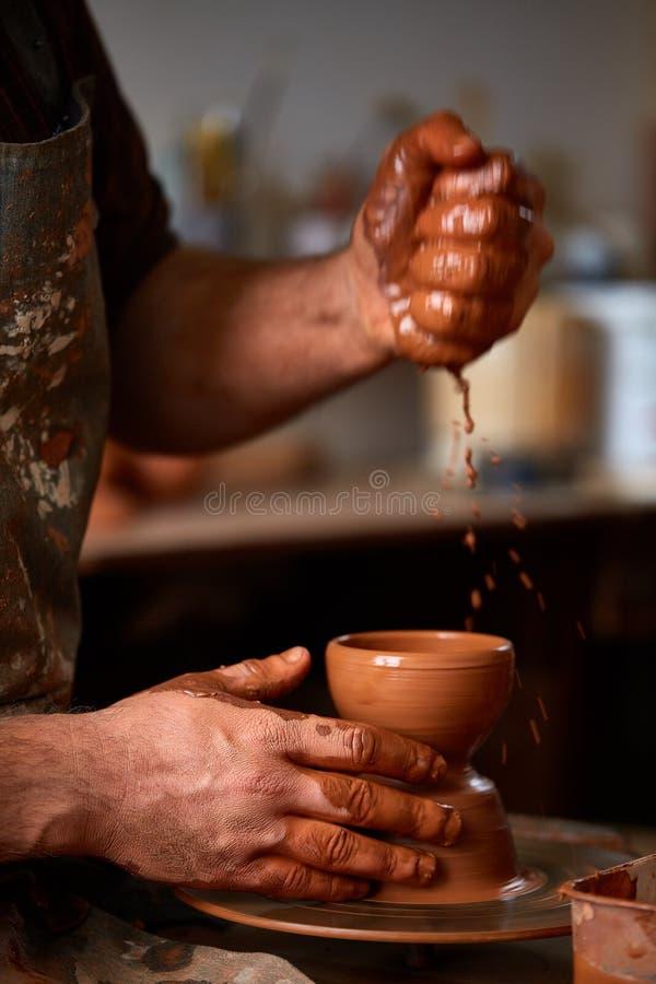 Zakończenie ręki męska garncarka w fartuch foremkach rzucają kulą od gliny, selekcyjna ostrość zdjęcie stock
