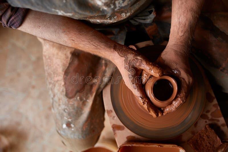 Zakończenie ręki męska garncarka w fartuch foremkach rzucają kulą od gliny, selekcyjna ostrość fotografia royalty free