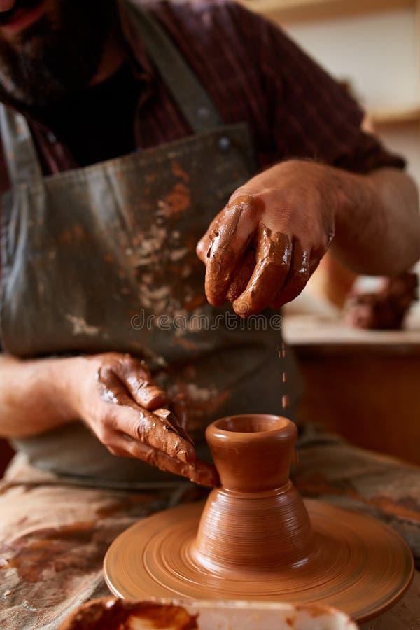 Zakończenie ręki męska garncarka w fartuchu robi wazie od gliny, selekcyjna ostrość obrazy royalty free