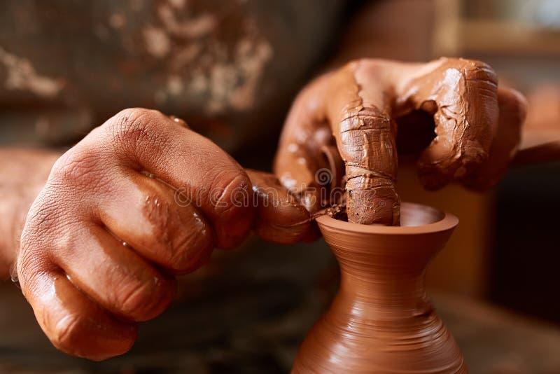 Zakończenie ręki męska garncarka w fartuchu robi wazie od gliny, selekcyjna ostrość fotografia royalty free