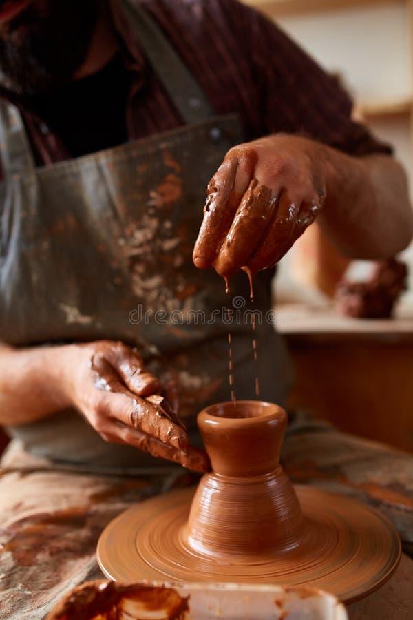 Zakończenie ręki męska garncarka w fartuchu robi wazie od gliny, selekcyjna ostrość zdjęcia stock