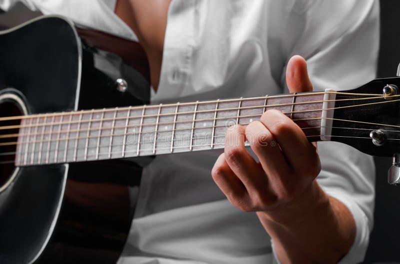Zakończenie ręki młody człowiek bawić się gitarę na czarnym tle Instrument muzyczny, sztuki pojęcie obrazy stock