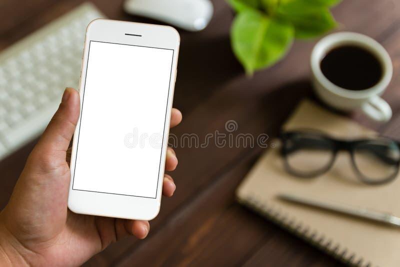 Zakończenie ręki mienia up telefon nad praca stołem obraz royalty free